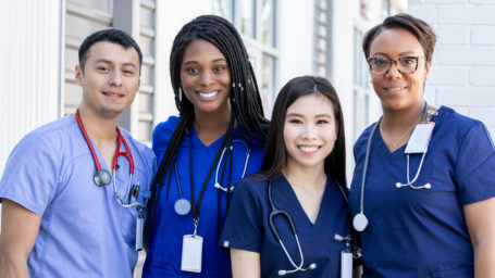 Diverse group of four nursing students standing together outdoors