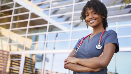 Portrait of smiling black female healthcare worker outdoors