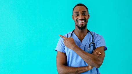Portrait of a smiling male doctor or nurse pointing with finger to side at studio copy space and looking at camera