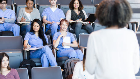 A class of attentive medical students listen to a mature female professor's lecture.